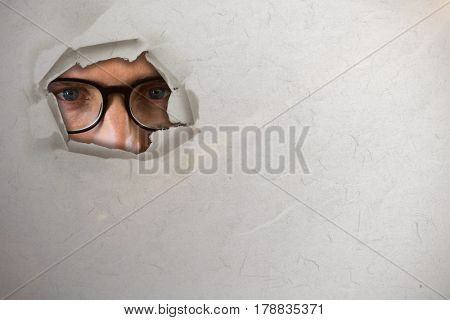 Close up portrait of man wearing eyesglasses against circle hole in paper 3d
