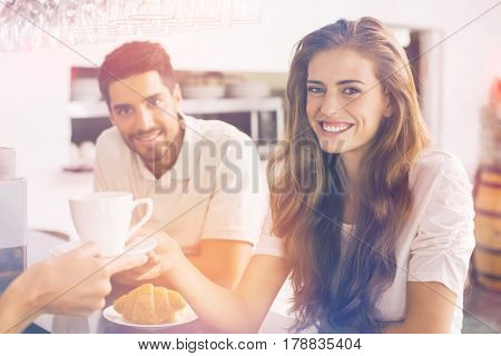 Graphic image of flare against couple eating breakfast and smiling at camera