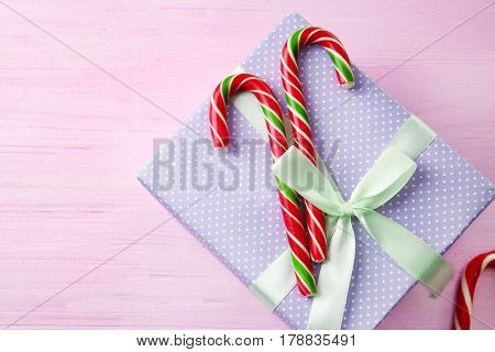 Christmas candy canes and gift box on color wooden background