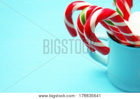 Christmas candy canes and marshmallows in cup on color wooden background