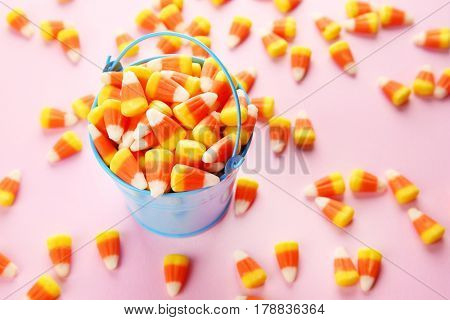 Bucket with tasty Halloween candies on light color background