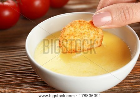 Dipping chips into bowl with cheese sauce on dining table