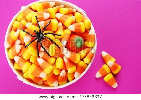 Bucket with tasty Halloween candies on color background, closeup
