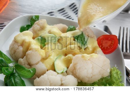 Pouring cauliflower with cheese sauce, closeup