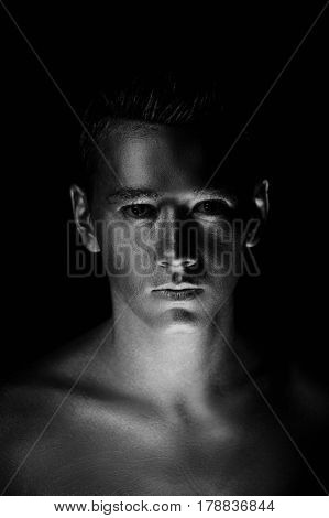 A handsome man of athletic build, completely covered in gold paint.Studio photos, With Hard lite, Black and white