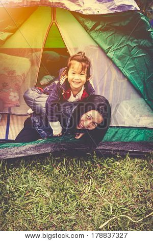 Vintage tone photo of happy asian family looking at camera on camping trip in their tent outdoors on summer morning with sunlight. Mother giving daughter piggyback ride and smiling happy together.