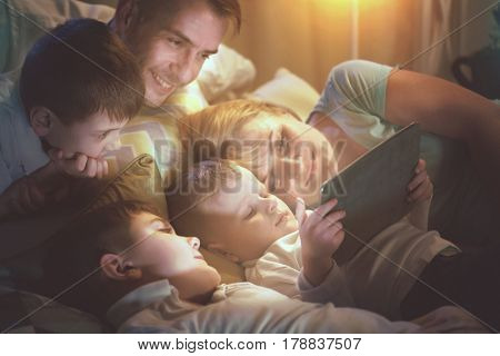 Happy family- Father, Mother and three kids lying down on the sofa and using tablet pc at night. Big Family together watching movie on tablet computer in dark room.