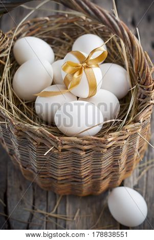 Easter Eggs in the Wattled Basket on Wooden Table