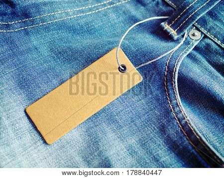 Label price tag on blue jeans from recycled paper. Mockup for price or brand presentation.