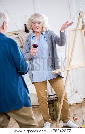 Emotional Senior Woman With Glass Of Wine Talking To Man