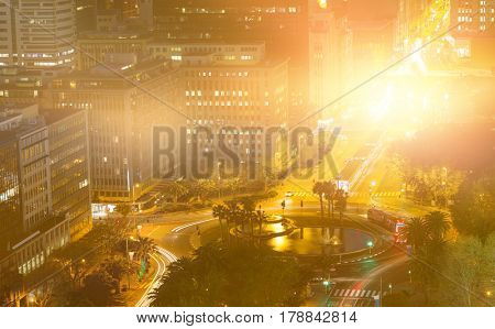 Blurry animated flare against illuminated roads by buildings in city