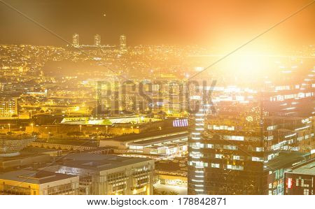 Blurry animated flare against high angle view of illuminated crowded cityscape