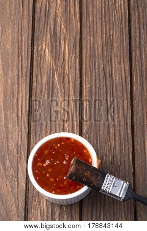 Barbecue sauce with basting brush over rustic barn wood table with room for copy space.