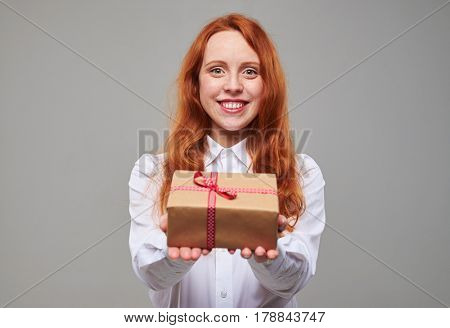 Close-up of pleased girl holding a present box. The concept of holidays and celebrations. Good-looking redhead teenager offers a gift box