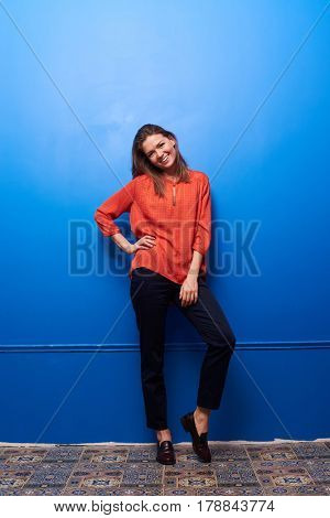 Full-length shot of a smiling girl posing on tiptoe isolated over blue background. Female wearing silk blouse and trousers looking at the camera