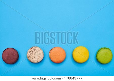 Top view of five colorful macaroons isolated over blue flatlay. Macaroon on turquoise flatlay