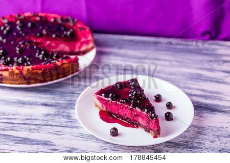 Piece Of Cheesecake On White Plate  With Currant On Colored Wooden Background.