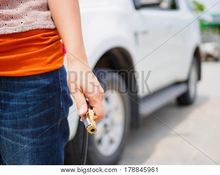 driver checking air pressure and filling air in the tires