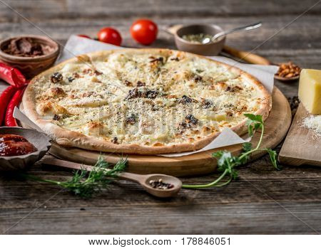 Pizza with four cheeses and pears and nuts served with pepper and cheese on side