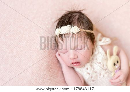 Baby girl in flowery hairband sleeping with her mouth open, holding her bunny toy, closeup