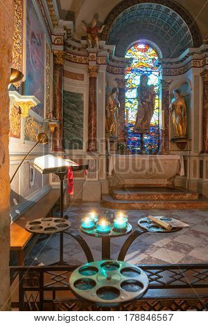 Gruissan, France - October 11, 2016; Sun streams through stained glass window backlighting statue of Virgin while candles create lens flare in foreground in ornately decorated Inside Church of Gruissan Notre dame de L'Assumption