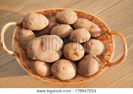 Raw potatoes in a basket on a wooden table