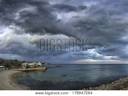 Exciting seascape with calm sea and stormy clouds