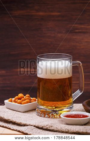 Glass of beer. Mexican salsa nuts. Appetizer with sweet salsa or chilli sauce. Mug or pint of ale. On rustic wooden background.