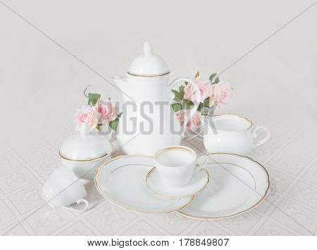 Classic white crockery for tea ore coffee: teapot coffee pot cup serving plate sugar bowl and creamer on a beautiful tablecloths