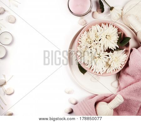 Spa setting with floating flowers and body care and cosmetic tools on shabby chic white background, top view. Wellness concept