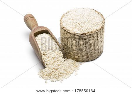 white rice in wooden scoopl and straw basket on white background