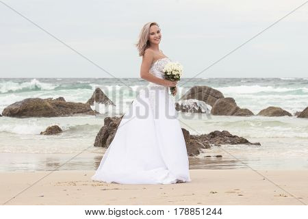 Beautiful bride at the beach with a flower bouquet.