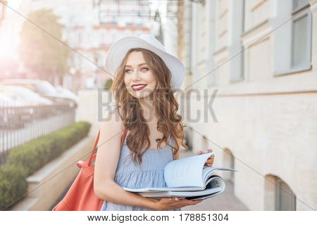 Cheerful lovely young woman in hat reading magazines on the street