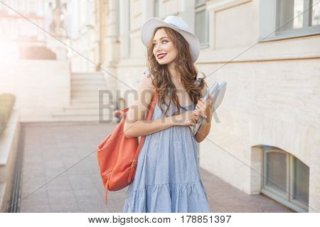 Cheerful attractive young woman with red backpack and book walking in the city