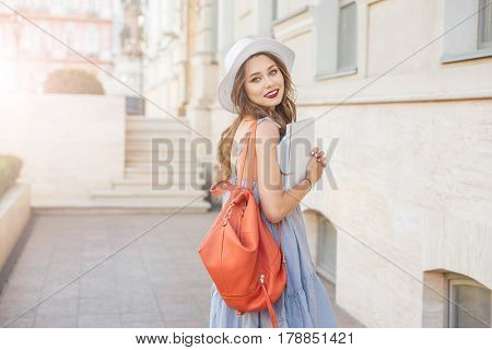 Happy beautiful young woman in hat with red backpack walking on the street