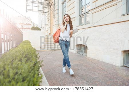 Young beautiful brunette girl talking on the phone and walking on the city street