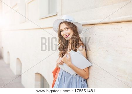 Happy attractive young woman in hat standing in the city and holding two blank covered magazines