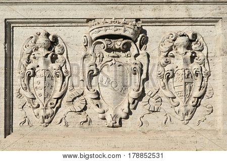 SPQR symbol of Ancient Roman Republic with other old noble emblems on Capitol Hill monumental staircase in Rome