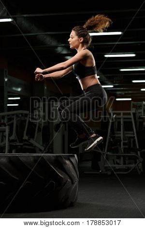 Photo of beautiful strong sports lady make sport exercises jumping in gym and looking aside.