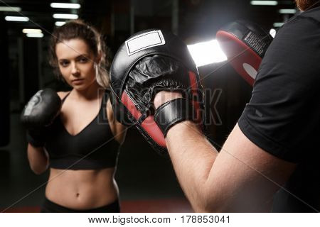 Photo of concentrated young strong sports lady boxer standing in gym with man trainer and looking aside. Focus on trainer's hands.