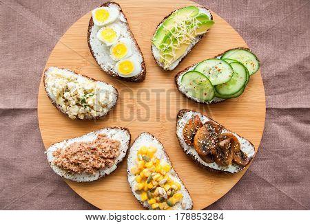 Mix Of Rye Bread Bruschettas With Various Filling. Sweet Corn Avocado Mashrooms Quail Eggs Cucumber