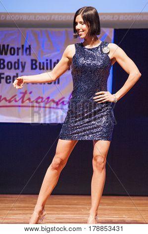 MAASTRICHT THE NETHERLANDS - OCTOBER 25 2015: Female figure model in evening dress shows her best in championship on stage at the World Grandprix Bodybuilding and Fitness of the WBBF-WFF