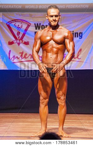 MAASTRICHT THE NETHERLANDS - OCTOBER 25 2015: Male bodybuilder flexes his muscles and shows his best front pose at the World Grandprix Bodybuilding and Fitness of the WBBF-WFF