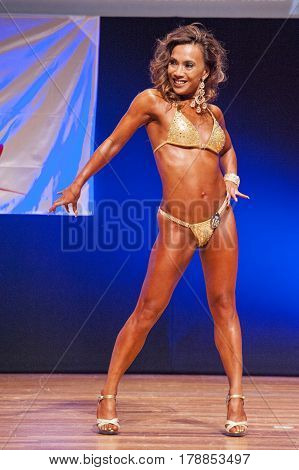 MAASTRICHT THE NETHERLANDS - OCTOBER 25 2015: Female physique model Esther Blom shows her best front pose at championship on stage at the World Grandprix Bodybuilding and Fitness of the WBBF-WFF