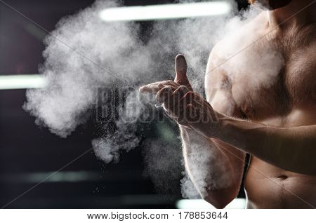 Cropped image of handsome sports man in gym rubbing hands with chalk