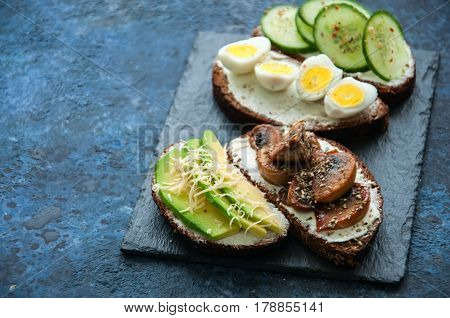 Mix Of Rye Bread Bruschettas With Various Filling. Avocado Mashrooms Quail Eggs Cucumber Cheese Sand