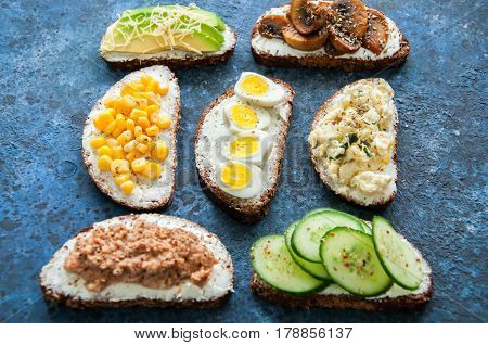 Mix Of Rye Bread Bruschettas With Various Filling. Sweet Corn Avocado Mushrooms Quail Eggs Cucumber