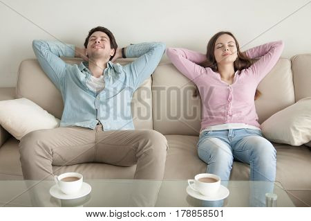 Happy young couple enjoying sitting on sofa at home, resting hands behind the head, relaxing with eyes closed, cup of coffee in the morning, dreaming of vacation, listening to music, leisure lazy day