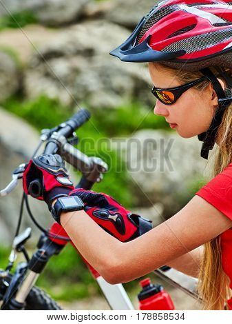 Woman traveling bicycle in summer park. Bicyclist girl watch on smart watches. Girl counts pulse after sport training and is looking for way to navigator. Cycling is good for health.