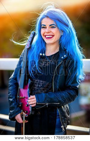 Blue hair woman buskers with violin outdoor in in sun shine. Girl perform music in sunrise or sunset.